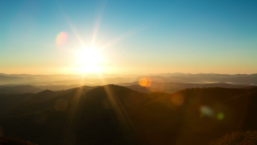 Time lapse of the sun rising from behind mountains. A beautiful lens flarees through frame. | Shutterstock HD Video #1008705070