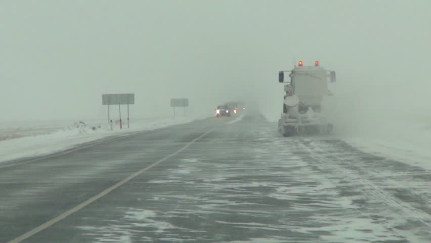 Movement of the car forward on the snow-covered Siberian route in a stream of trucks, at squally lateral wind | Shutterstock HD Video #1008713890