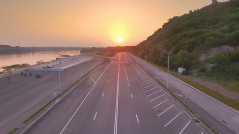 AERIAL: New asphalt road on the embankment of the river Ufa. Beautiful sunset landscape of the river and the city of Ufa.