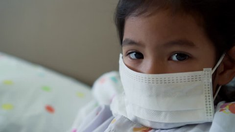 Sick asian little child girl wear protection mask while live in the hospital in slow motion shot