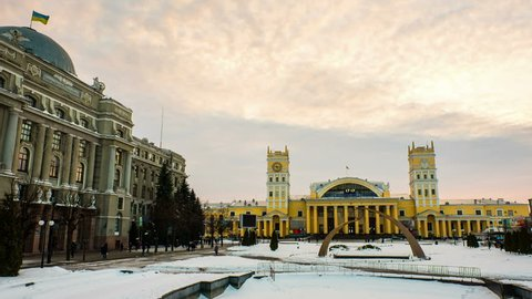 Kharkiv, Ukraine. Railway station in Kharkiv, Ukraine, at sundown on a snowy cloudy day. People walking by, time-lapse