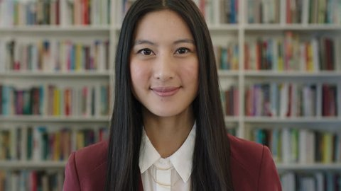 portrait of cute young asian woman student smiling confident looking at camera in public library bookshelf background learning research