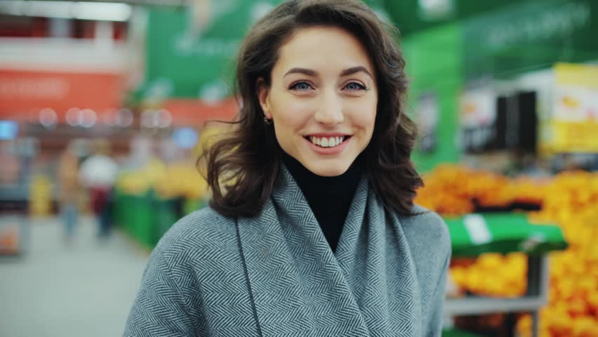 Portrait young woman stands in front of the camera and smiles while in a produce section in supermarket feel happy girl shopping face retail store pretty customer happiness casual market food consumer
