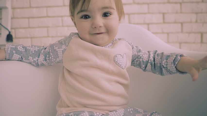 Cheerful little brunette baby girl sitting on white chair with smile slow motion. the child tries to reach out to the camera. | Shutterstock HD Video #1008761360