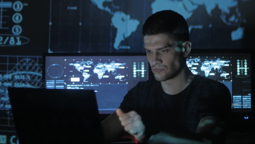 Male hacker programmer working at computer while blue code characters reflect on his face in cyber security center filled with display screens. | Shutterstock HD Video #1008776780