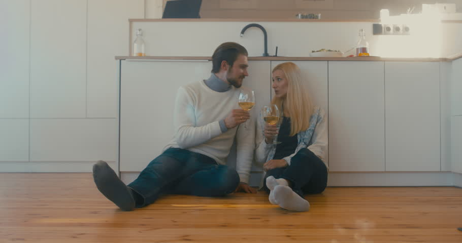 Young adult beautiful Caucasian couple celebrating something at home, drinking wine on the floor. 4K UHD   Shutterstock HD Video #1008781850