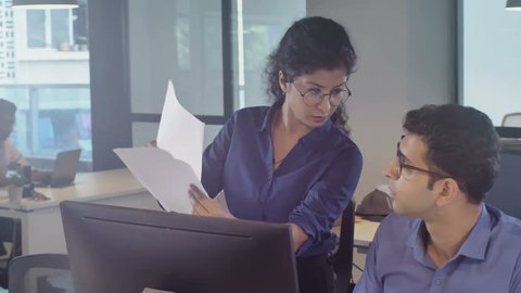 Young and strict female boss criticizing and scolding a young member of staff or subordinate sitting in front of the computer screen after dissatisfied with bad work results, in a modern office setup