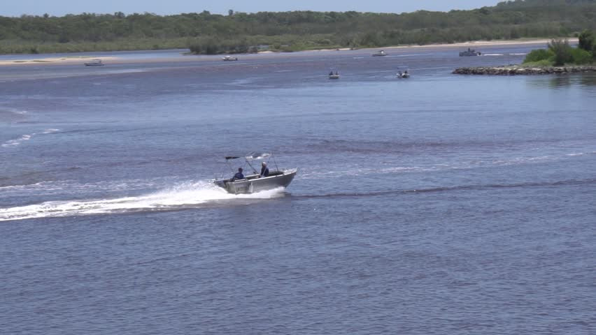 Two people men travel along a river in an aluminum aluminium dinghy boat with outboard with bush forest on riverbanks on a sunny day.