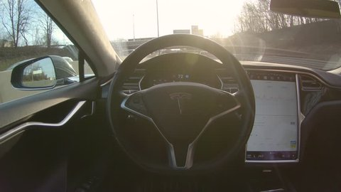 TESLA AUTONOMOUS CAR, MARCH 2018: LENS FLARE: Modern electric car with no driver drives along busy motorway. High technology robotic car operates itself on sunny morning highway full of commuters.