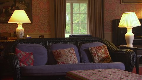 Still shot of a vintage living room with a couch, ottoman, tables and  lamps. old wall paper and paintings can be seen.