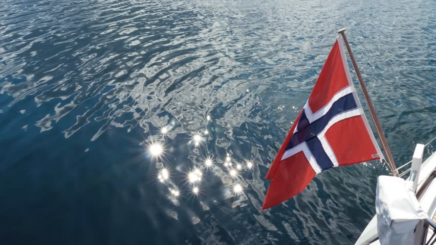 Norway flag on ship, Red with blue and white cross. Norwegian national flag on stern of boat. Blue clear sea water. Waves in pond, reflection of sun's rays. Travel on Norwegian fjord in good weather