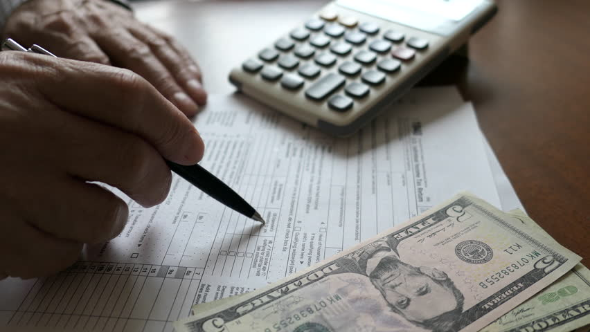A Elderly Man Reads Income Tax Return Refund Forms 1040. Calculator, Dollars On The Table