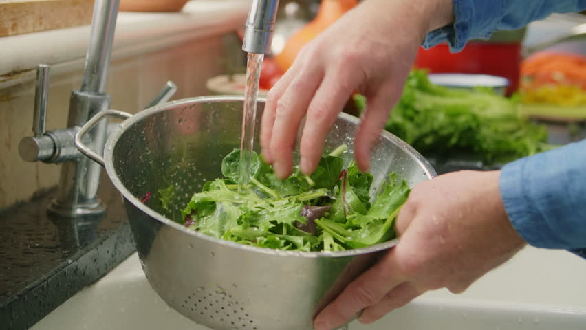 Closeup Of Man Hands Washing Green Leafy Vegetable In Colander