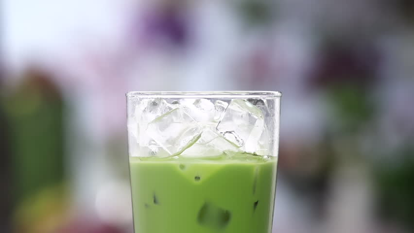 close up Pour milk into a glass of green ice tea,  Slow motion shot