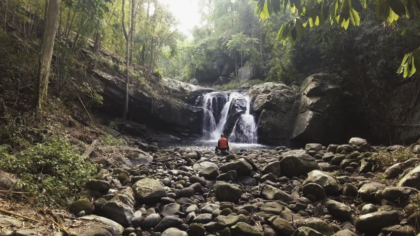 cinemagraph of man sitting on a rock in front of waterfall in tropical forest at early morning