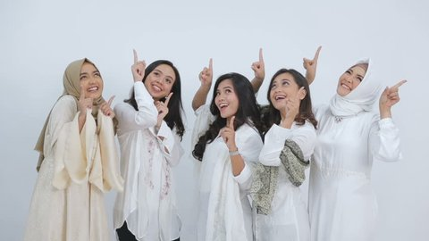 Portrait of a group of beautiful muslim female friends smiling pointing up  to free space