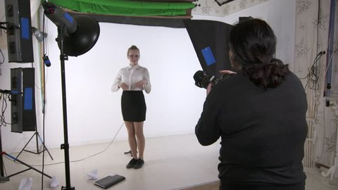 Studio photography. Young model poses for photographer in photo studio. Woman photographing teen girl in white shirt on set in photo studio. Backstage shot during indoor photoshoot.