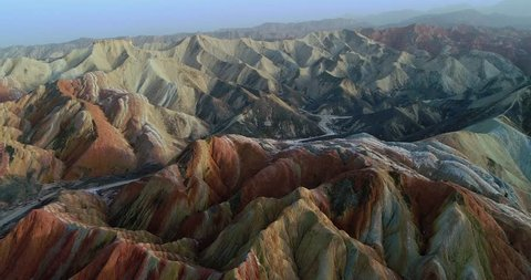 Flying drone over Rainbow mountains. Aerial view on most beautiful section of Zhangye Danxia Rainbow Mountains showing hills covered with multicolored pattern.
