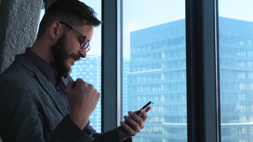 Business success and achievement - happy businessman cheering celebrating on cell phone. Young urban professional successful business man reaching personal goals. Smartphone app or video game concept | Shutterstock HD Video #1008983720