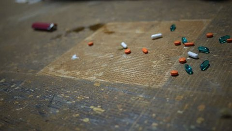 Camera slides across prescription pills on the floor of a trap house
