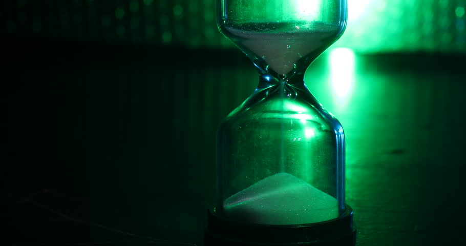 Time concept. Silhouette of Hourglass clock on dark toned backlight background. Time is money for business ideas. Sands move through hourglass. Time is running out. Slider shot.