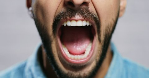 Closeup of angry man. Italian fuy showing fear, rage and frustration. Slow motion