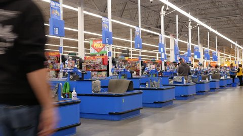 Port Coquitlam, BC, Canada - March 20, 2018 : Motion of people paying foods at check out counter inside Walmart store with 4k resolution