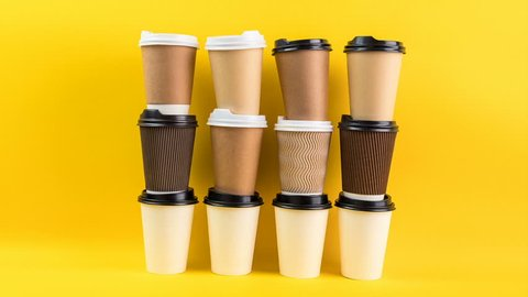 A lot of disposable cups for coffee and tea change places. Nice catering for a coffee shop. Video footage stop motion timelapse. Bright yellow background. Coffee take away ( to go )