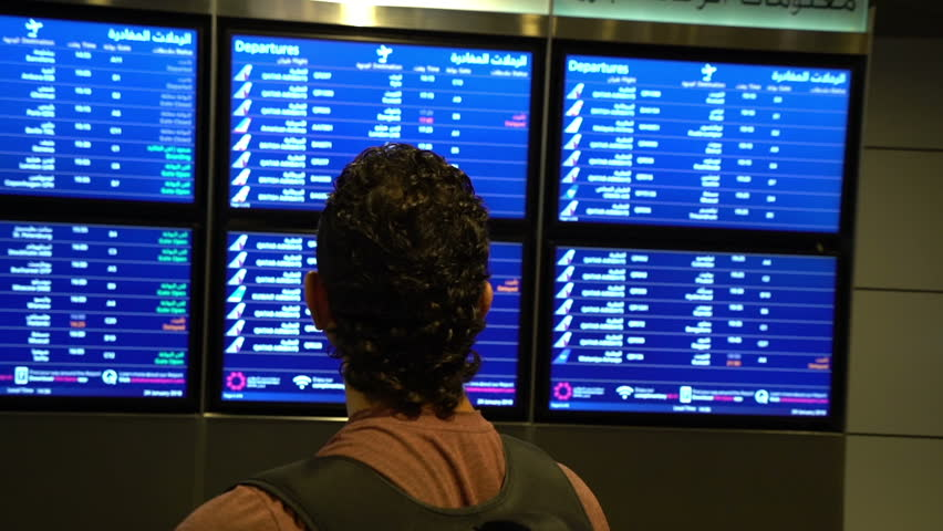Man passenger looking at timetable board screen at the airport terminal, international flight, business man travels abroad concept | Shutterstock HD Video #1009028900