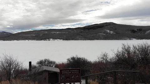Aerial footage filmed by a drone flying out from shore over a frozen lake in Colorado. Filmed on the Grand Mesa at the end of Winter.