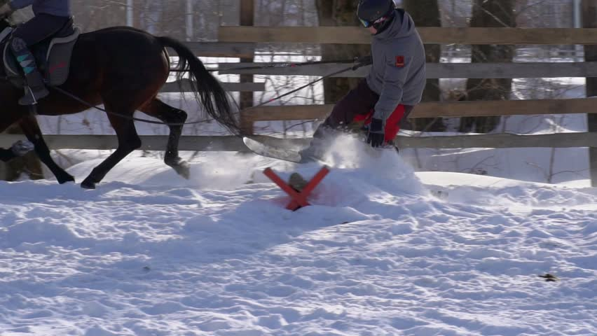 SLOW MOTION : A girl galloping on a horse at a gallop. A horse is dragging a snowboarder guy on a rope. Snowboarder rides on a snowboard in snowdrifts. Girl jockey and guy snowboarder work out a jump