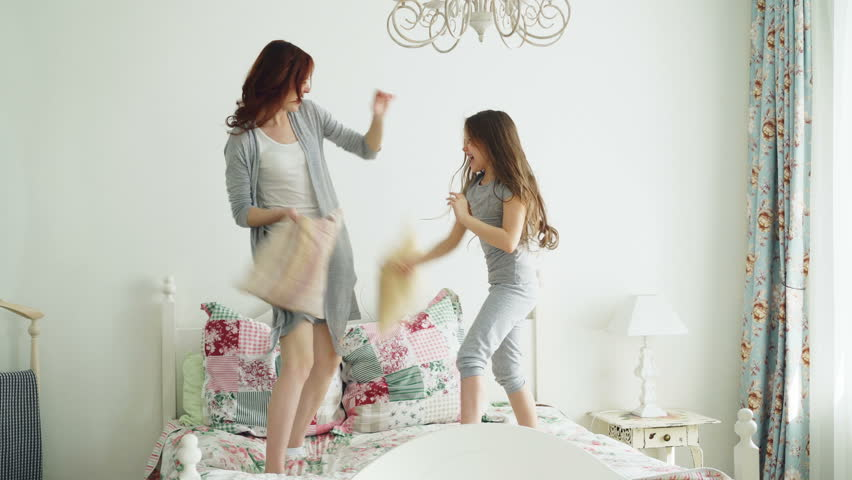 Happy little daughter and young mother in pajamas fighting pillows on bed while have fun in cozy bedroom during vacation at home | Shutterstock HD Video #1009068740