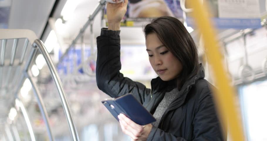 Japanese woman using smart phone on train in Tokyo, Japan