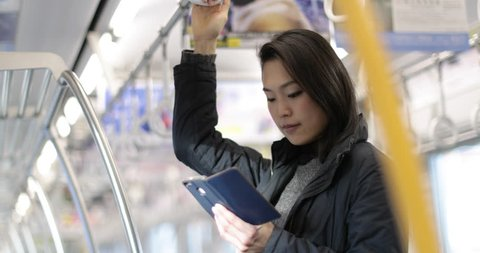 Japanese woman using smart phone on train in Tokyo, Japan