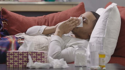 Man laying on a sofa coughing and sneezing