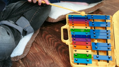 Playing music instrument. Closeup boy and teacher's hands playing on xylophone.