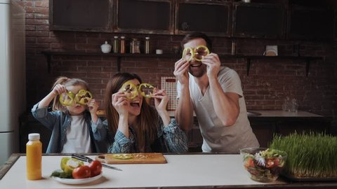 Funny, young and cheerful family, are playing with paprika in the kitchen while cooking