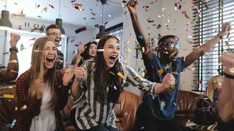 Emotion. African American fans celebrate victory confetti 4K close-up. Diverse supporters go crazy watching sports on TV