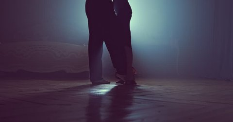 Close-up of legs of dancing couples in the smoky studio. Slow motion. Silhouette