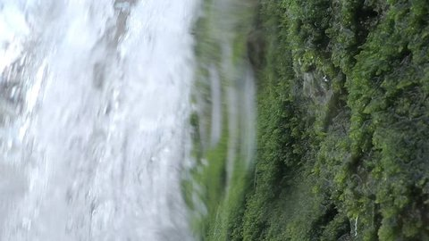 Water river falling from inside a waterfall in slow