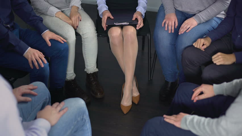 Close-up of people sitting in circle and holding hands at therapy session