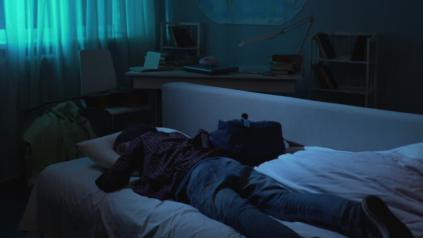 Over exhausted male teen coming from school and falling bed in clothes, long day | Shutterstock HD Video #1009141940