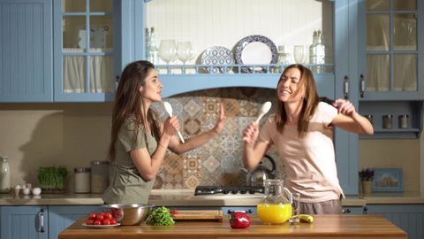 Portrait of two beautiful women dancing and singing at home kitchen using spoons, while cooking healthy breakfast with fresh vegetables and fruits slow motion