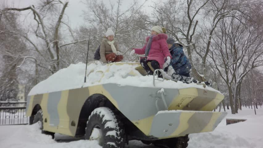 Children in the infantry fighting vehicle. War in Ukraine. It's snowing, it's cold. Combat reconnaissance and sabotage machine