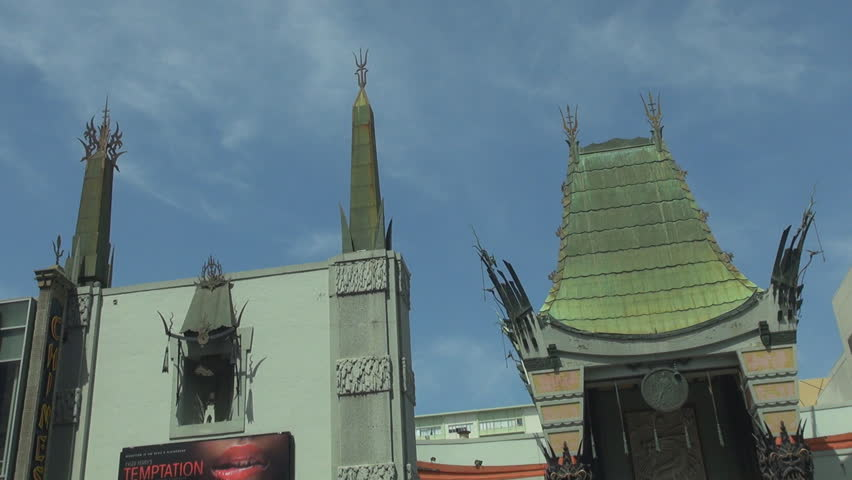 Pan right of Chinese theatre with asian rooftop design by day, Hollywood icon in Los Angeles