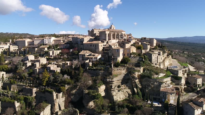 Aerial view of Gordes, labelled Most Beautiful Villages of France, perched on a rocky outcrop at the end of the Vaucluse plateau, dominated by its Renaissance castle and its romanesque church St Firmi