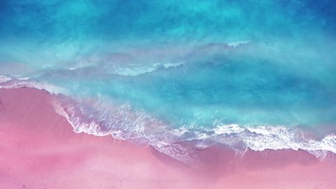 Aerial view of ocean waves break on tropical sand beach. Looping Water texture, Sea side and pink sand beach, Sunset  beach seamles loop background.