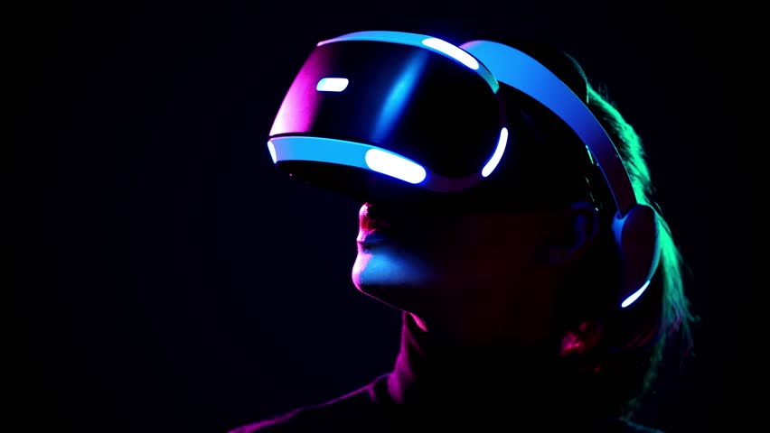 Young woman in VR headset looks around and wonders how amazing. Virtual reality helmet on black background #1009215590