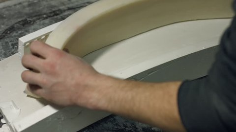 Close up molding a gypsum cornice. Mans hands holding silicone mold for producing cornice. Production of luxury frames.