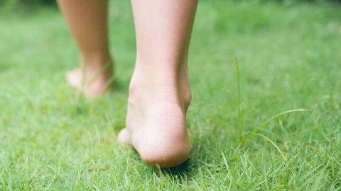 Young Woman Walking Bare Feet on Green Grass Field. 4K, Slowmotion.